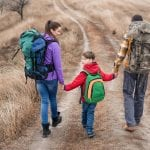 Family hiking along grass path through field