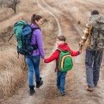 Family hiking along grass path through field