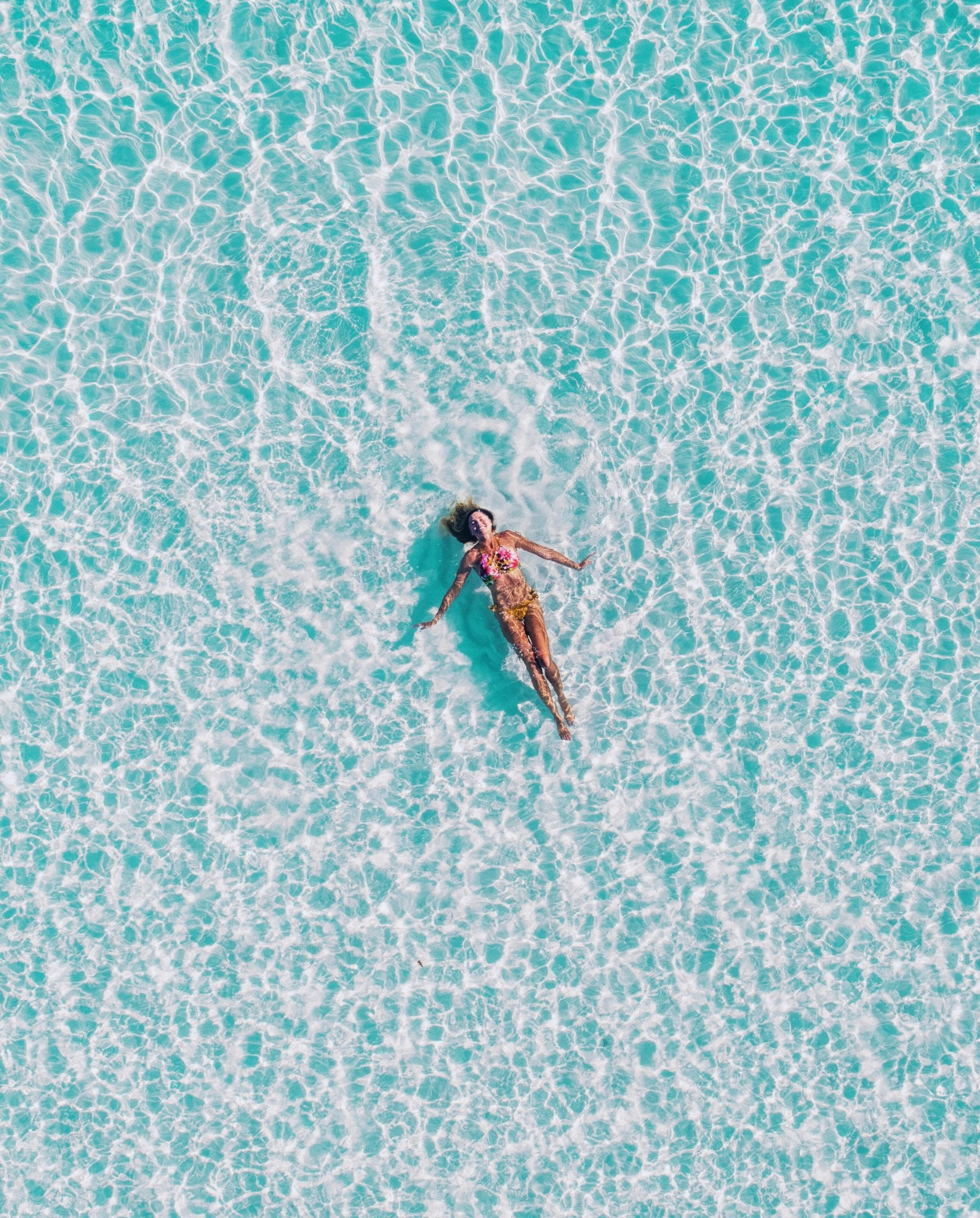 Woman floating in clear shallow water