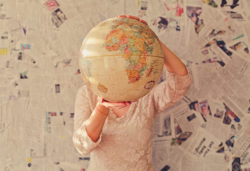 Woman holding globe in front of face