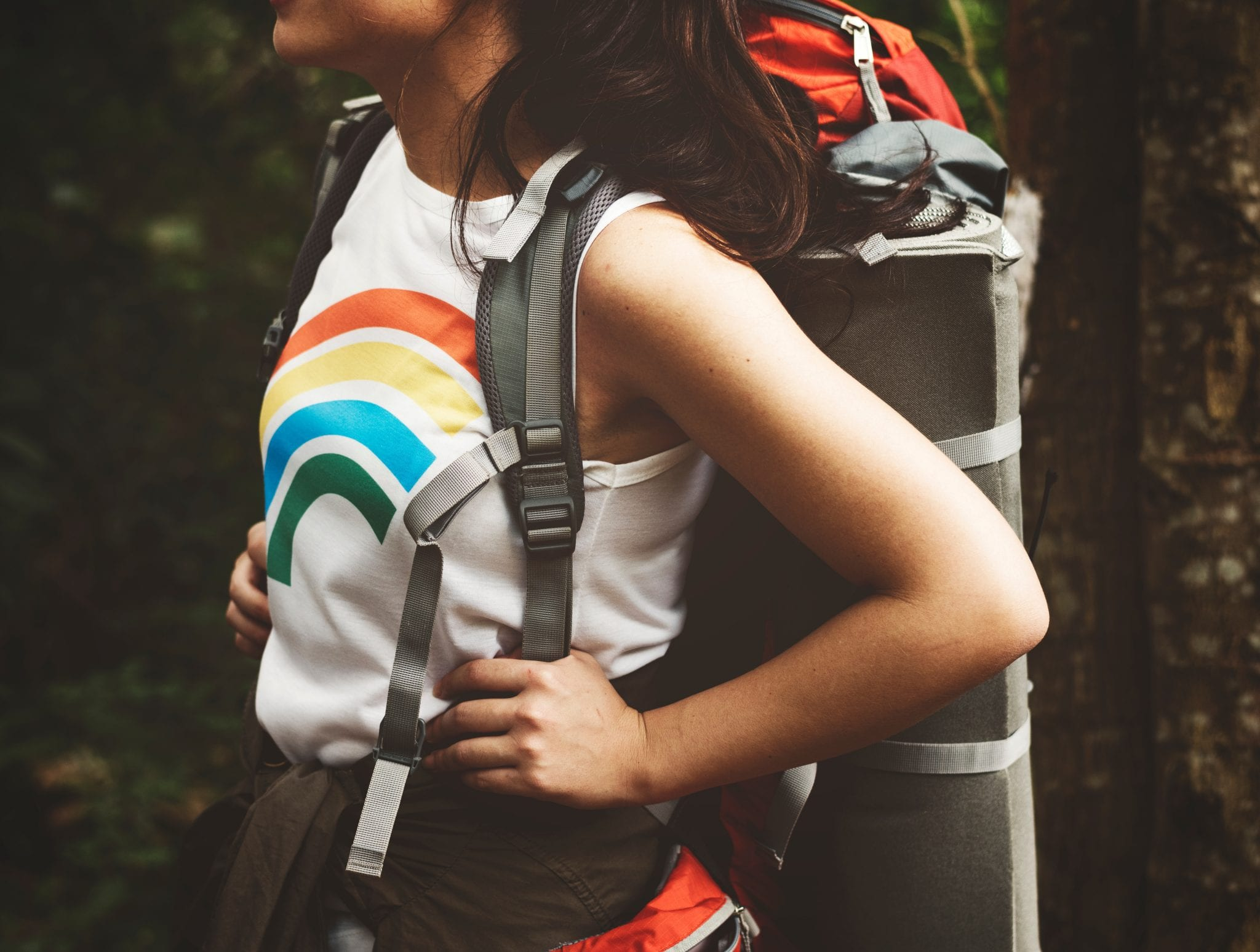 Young woman with backpack and rainbow shirt