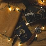 Passport camera and journal spread on table with Christmas lights