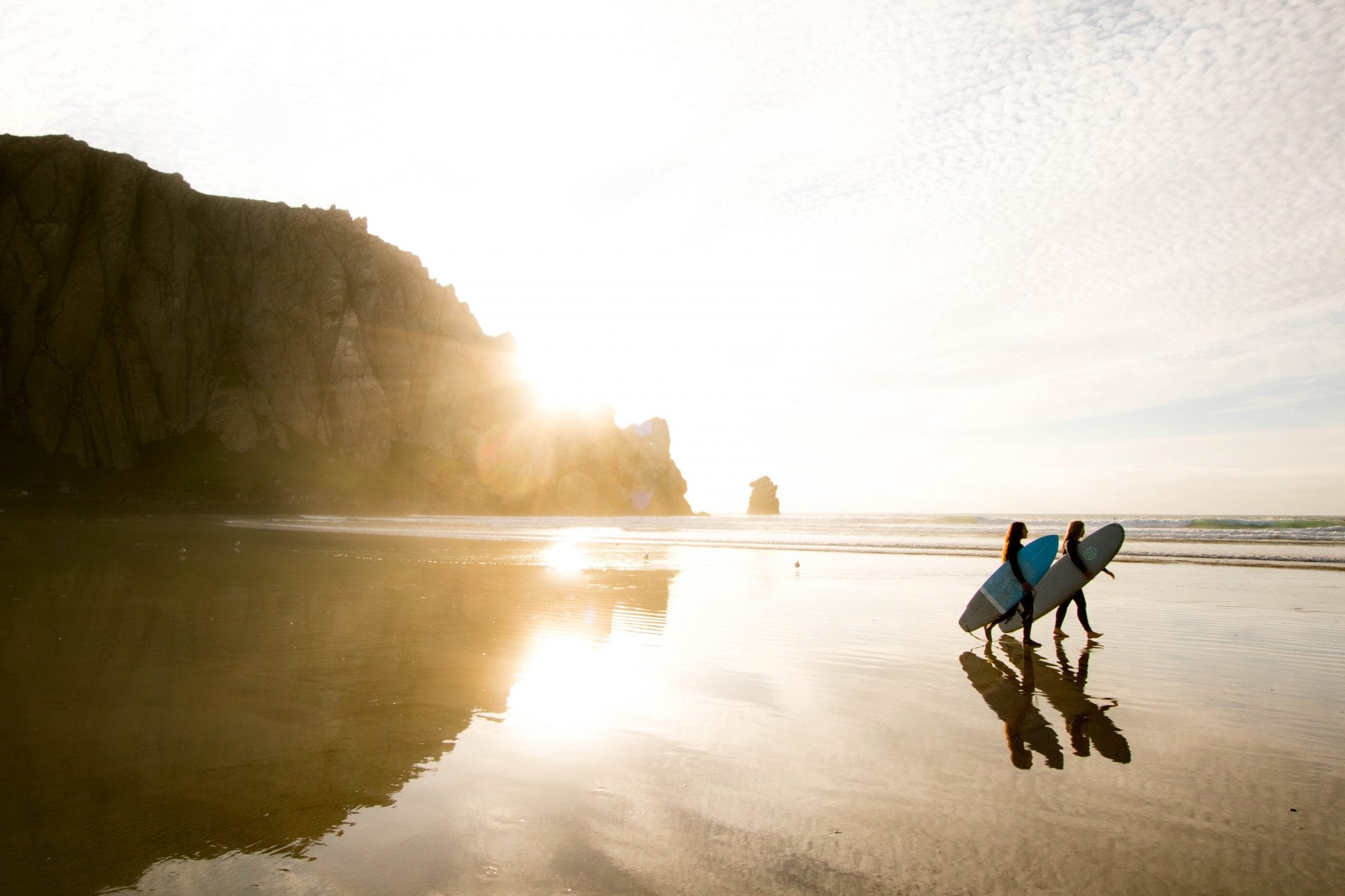 Surfers walking along beach at sunrise