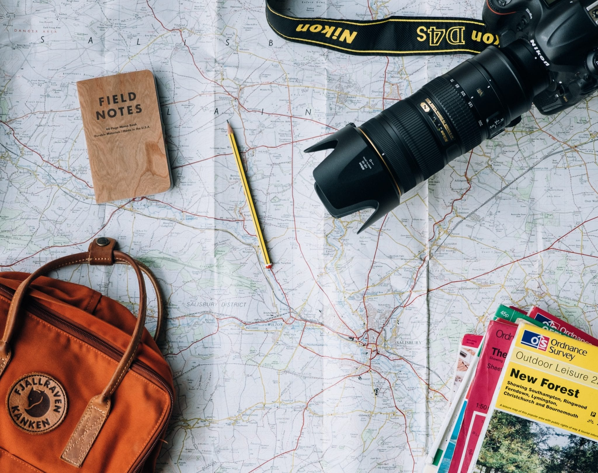 Travel planning items spread on map