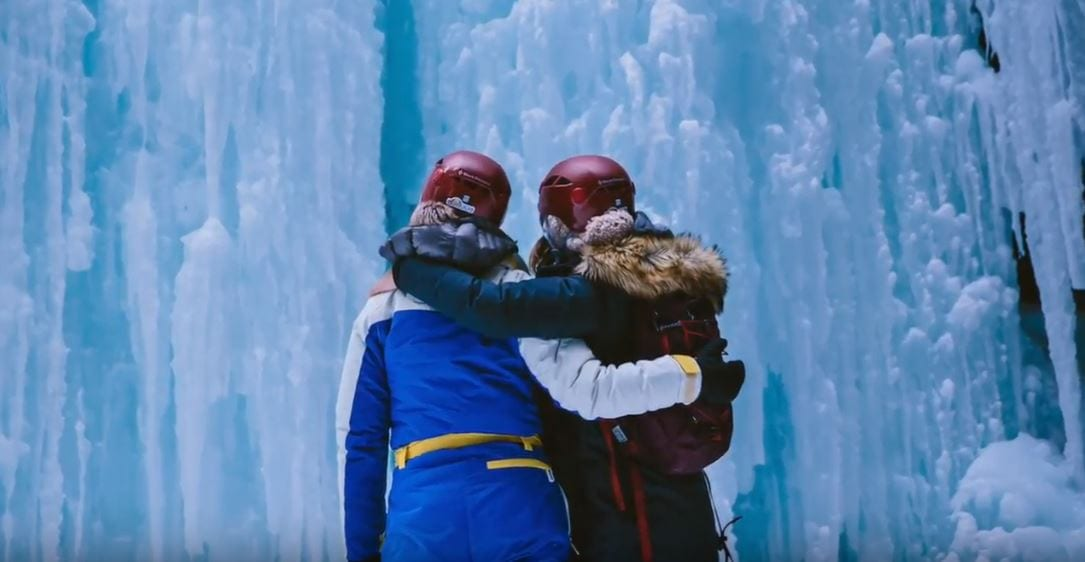 Two women standing in front of frozen waterfall