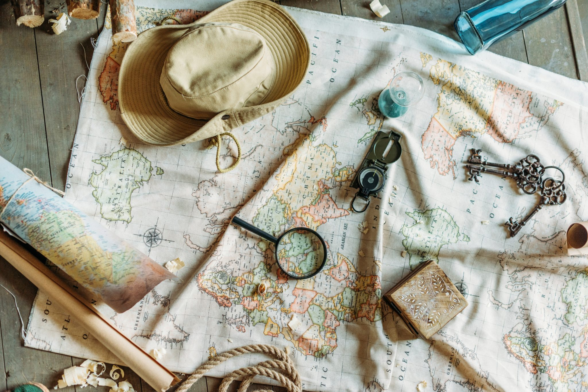 Travel planning gear spread out on map