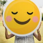 Woman carrying happy face emoji