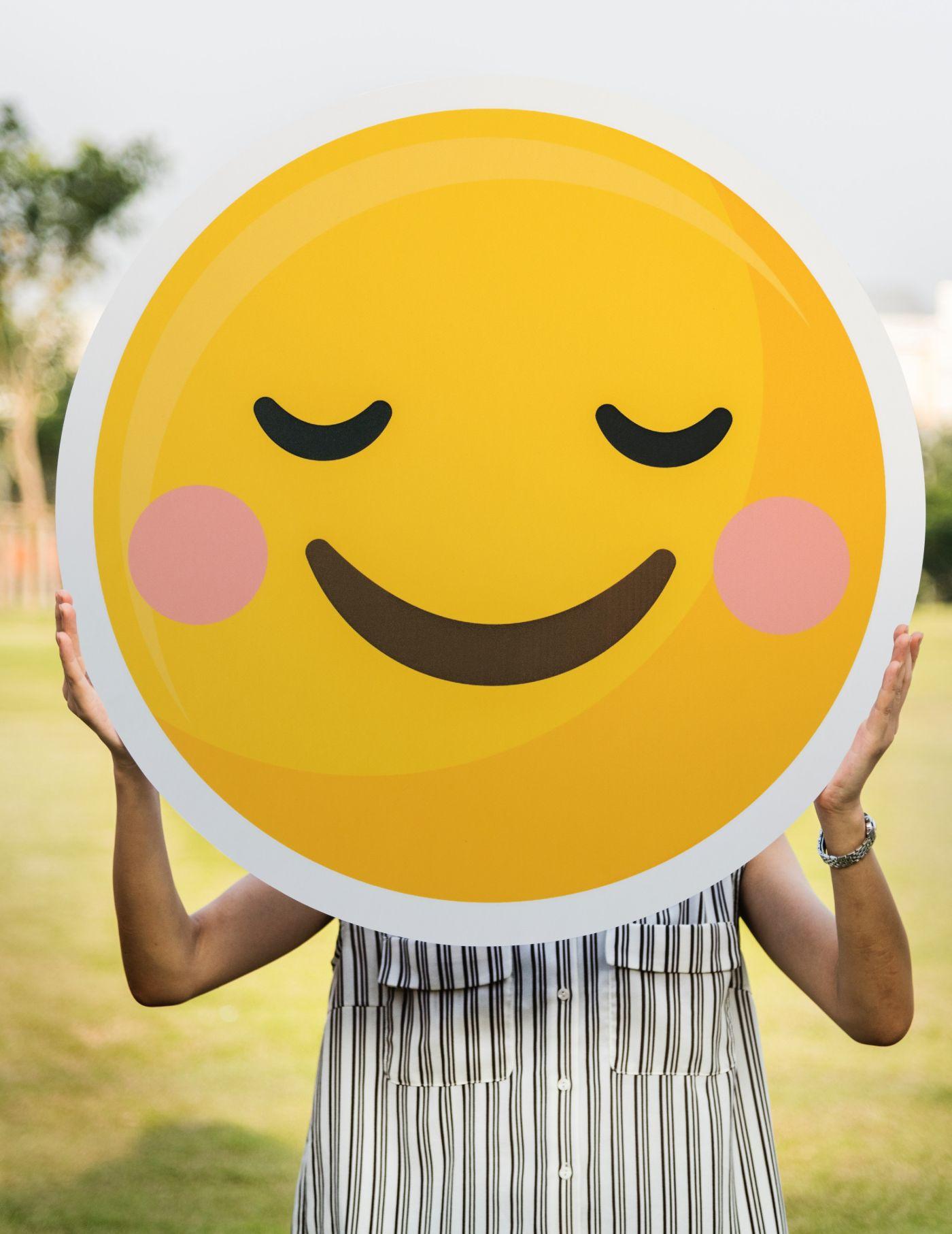 Woman carrying happy face emoji